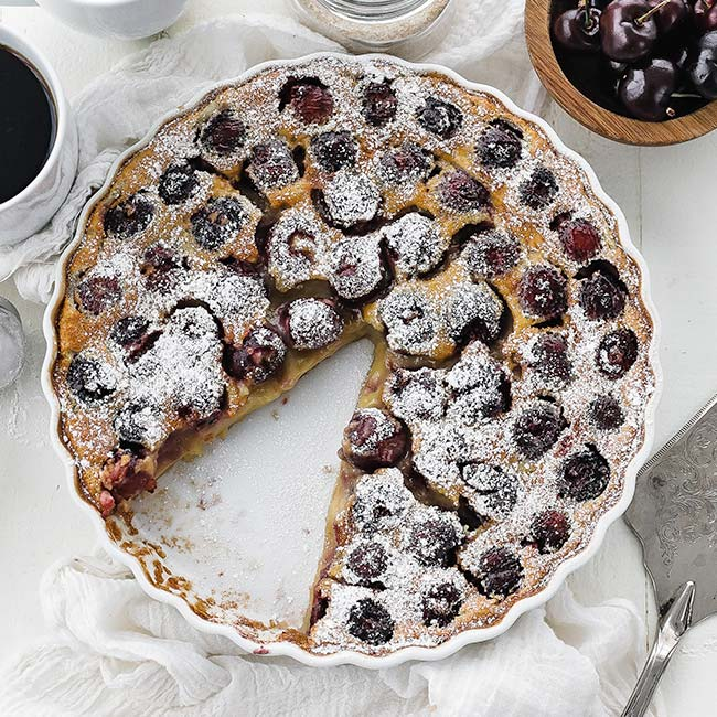cherry clafoutis in a glass tart pan with powdered sugar