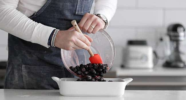 adding blackberries to a casserole dish