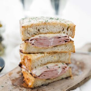 stacked ham and cheese croque monsieur sandwich on a cutting board
