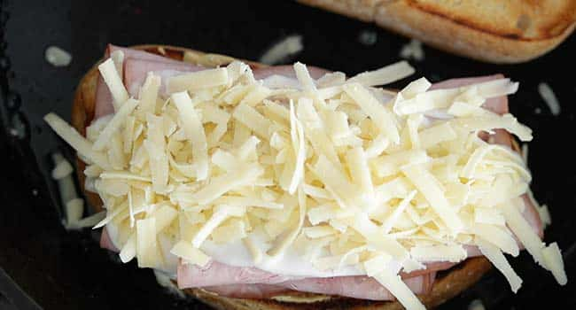 shredded comte cheese on a ham sandwich with bechamel