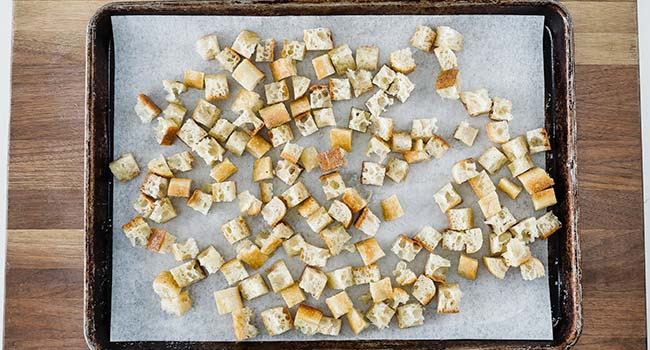 croutons spread out on a cookie sheet tray with parchment paper