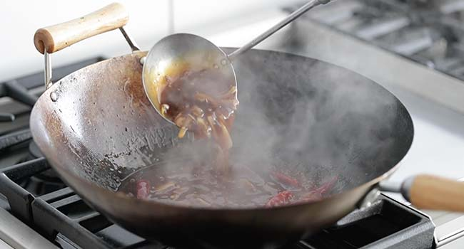 stirring a sauce with onions in a wok