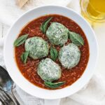 bowl of tomato sauce with spinach gnudi