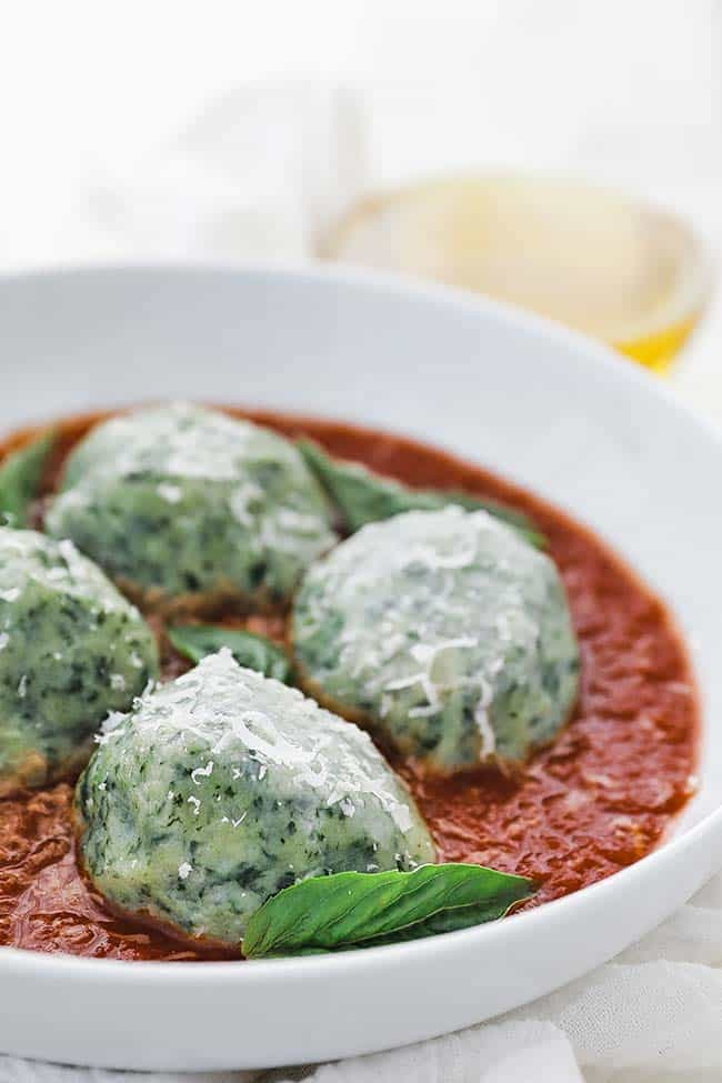 gnudi with pomodoro sauce in a bowl with parmesan cheese and basil