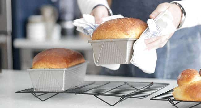 setting cooked brioche bread in a pan onto a cooling rack