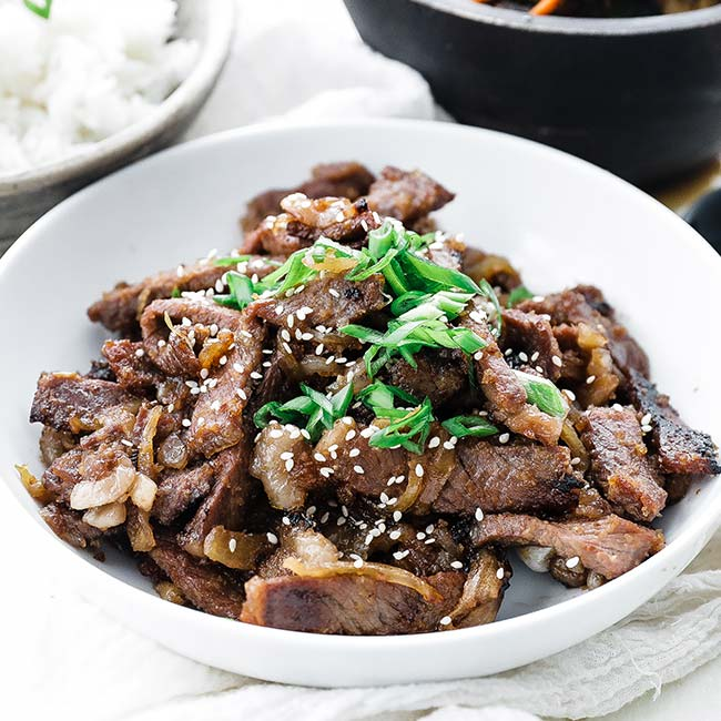 bowl of thinly sliced beef bulgogi with green onions