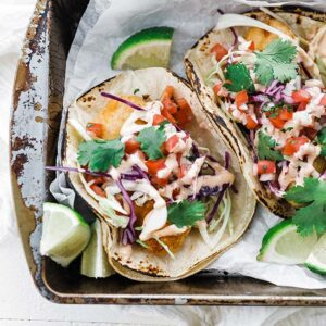 fish tacos on parchment paper with salsa and chipotle mayo