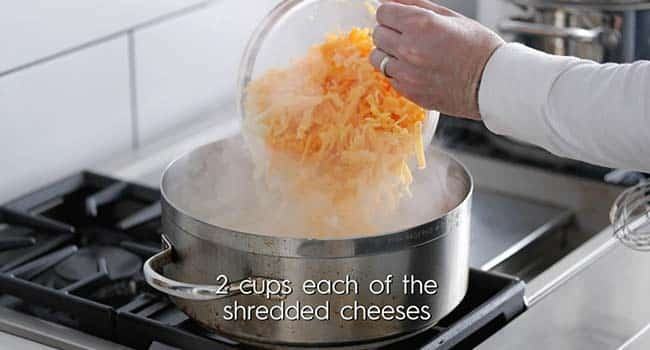 adding shredded cheese to a large pot with milk