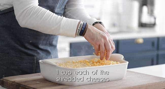 sprinkling cheese on top of macaroni and cheese in a casserole dish