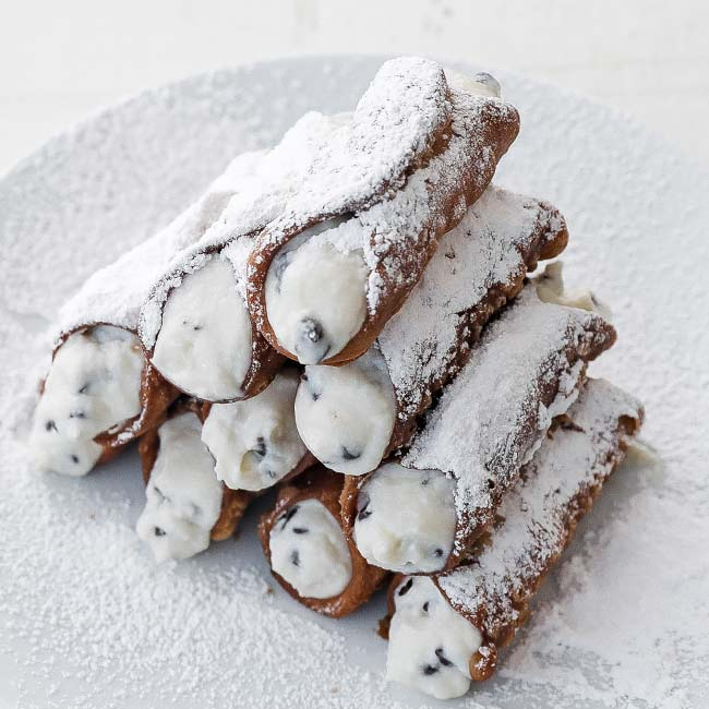 stacked up cannolis on a plate with powdered sugar