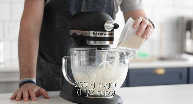 mixing ricotta in a stand mixer while adding in sugar