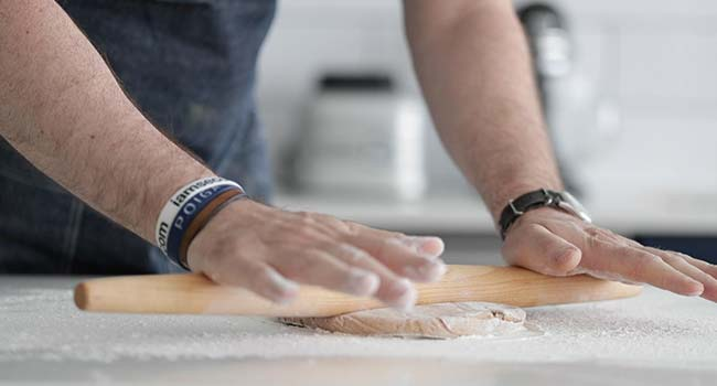 rolling out cannoli dough on a floured surface with a rolling pin