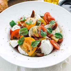bowl of sliced tomatoes, cheese and herbs