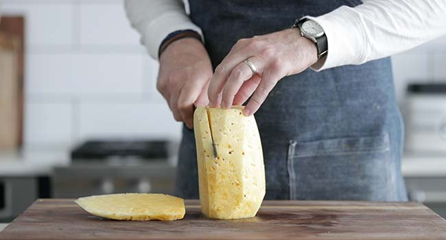 slicing a peeled pineapple on a cutting board