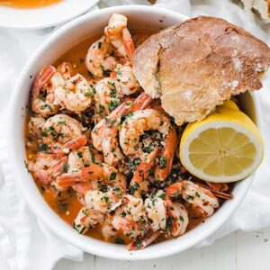 bowl of shrimp scampi with bread and lemon