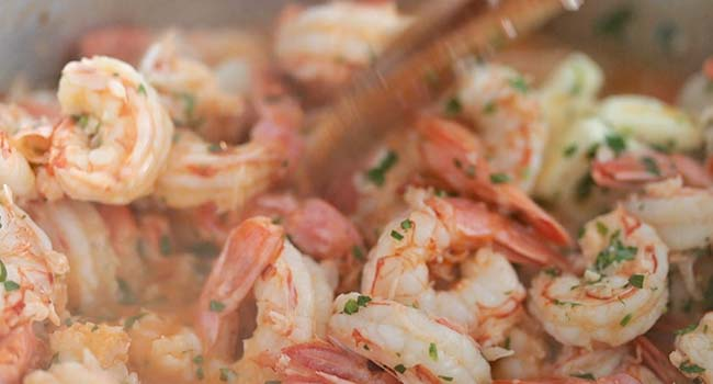 cooked shrimp with parsley and butter in a pot