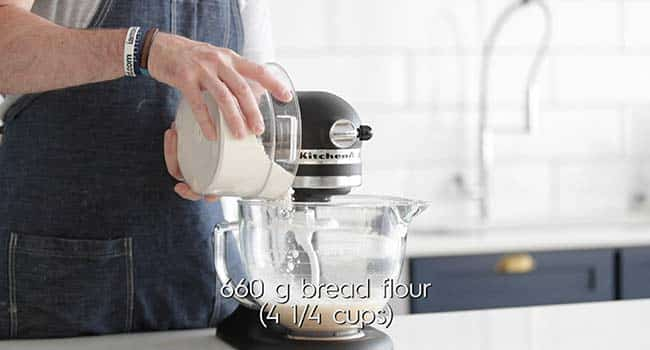 adding flour to a stand mixer