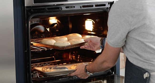 adding bagels on a sheet tray to the oven