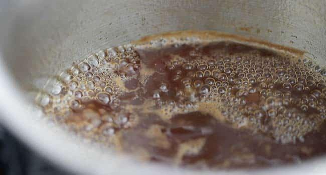 dark rum sauce simmering in a pot