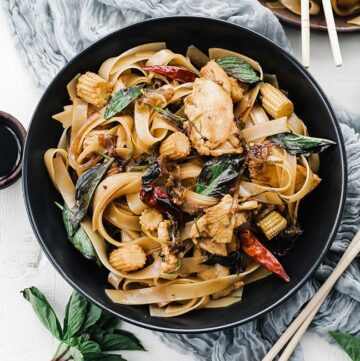 bowl of drunken noodles with chicken and basil