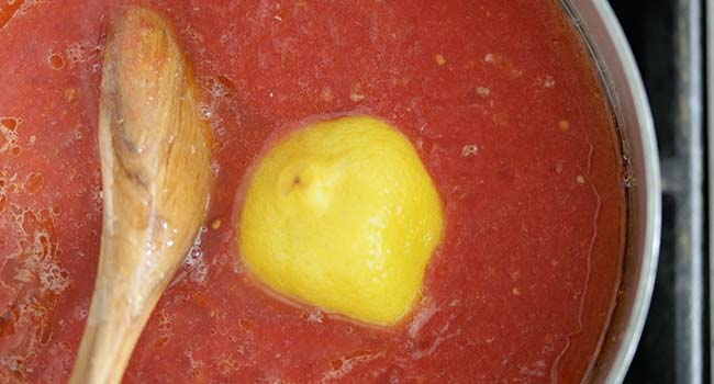 adding lemons to tomato sauce in a pot