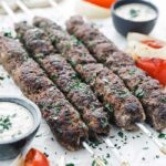beef kebabs on parchment paper with vegetables