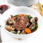 bowl of coq au vin with carrots and mushrooms