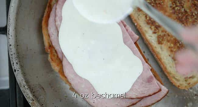 placing ham slices and bechamel sauce onto toasted piece of bread
