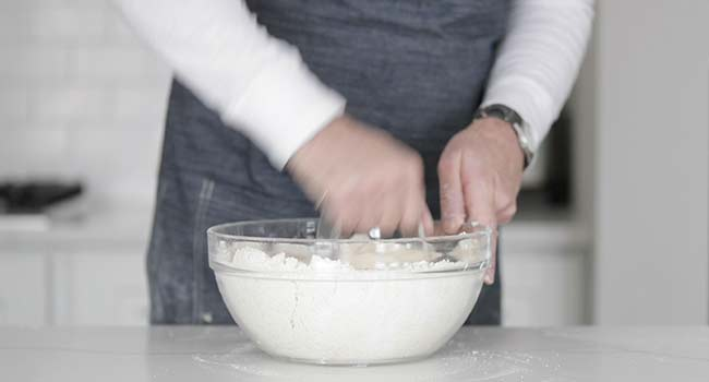 cutting butter with flour in a bowl using a pastry knife