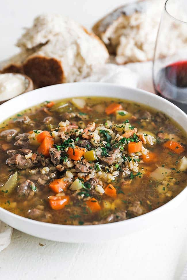 bowl of beef stew and barley with herbs and bread