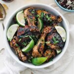 bowl of grilled jerk chicken with limes